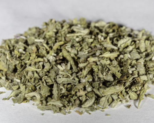 An angled front photograph of a small pile of cut and sifted Turnera Diffusa (Damiana) herb.
